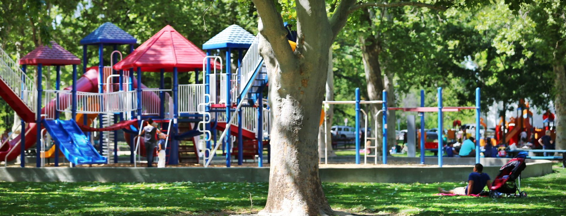 A shady afternoon escape from the heat as a father watches his children play at Royer Park in Roseville, California